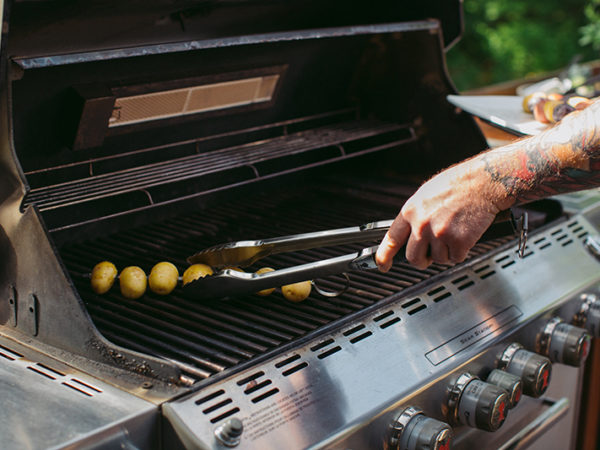 Potatoes on a skewer on a grill being flipped with a pair of tongs.