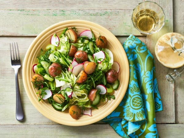 A colorful and fresh mixed green salad with delicious, heavenly Creamer potatoes.