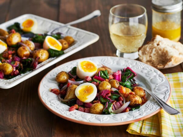 Two plates of colorful soft boiled eggs with Swiss chard and Creamer potatoes.